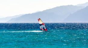 ??n surferritten in het Rode Overzees tegen de achtergrond van een rotsachtige kust in Egypte stock foto's