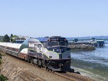 JUL 14, 2018: Amtrak 90250. Jul 14, 2018; Edmonds, WA, USA; AMTK 90250 NPCU trailing Amtrak`s Cascade Service 517 passes the Edmonds waterfront on a clear summer stock photos