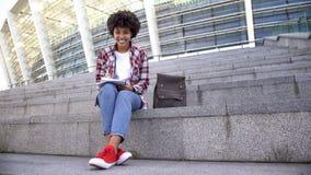 N?tt afro--amerikan kvinnlig student som utomhus g?r l?xa och att le in i kamera arkivfoto