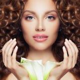 n?tt framsida Perfekt modellkvinna med lockigt hår, klar hud och blomman royaltyfri fotografi