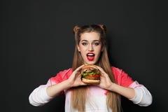 N?tt kvinna med den smakliga hamburgaren arkivfoto