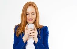 N?tt r?dh?rig manflicka med att le f?r telefon som isoleras p? vit bakgrund Den unga r?vaktiga kvinnlign i aff?rsdr?kt, har f?rbl fotografering för bildbyråer