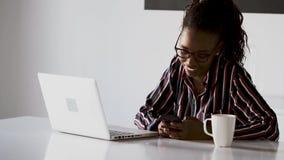 N?tt ung aff?rskvinna som anv?nder hennes smartphone, medan arbeta med b?rbara datorn i kontoret stock video