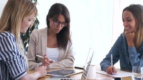 N?tt ung aff?rskvinna som visar framsteg av arbete i digital minnestavla till medarbetare i kontoret lager videofilmer