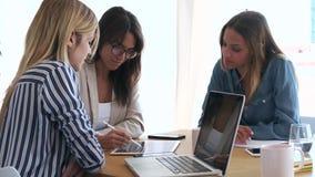 N?tt ung aff?rskvinna som visar framsteg av arbete i digital minnestavla till medarbetare i kontoret stock video