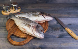 N a wooden table cutting board with fresh raw dorado fish gutted. Near the knife, salt and pepper Stock Photo