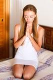 Na łóżku młodej kobiety modlenie obrazy royalty free