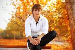 Na ławce młodego człowieka obsiadanie, Zdjęcie Royalty Free