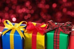 Na światła czerwonym rozmytym tle trzy prezenta. Obraz Stock