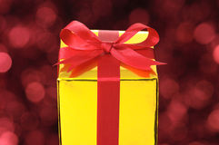 Na światła czerwonym rozmytym tle złocisty prezent. Zdjęcia Stock