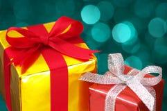Na światła rozmytym tle złociści i czerwoni prezenty. Obrazy Stock