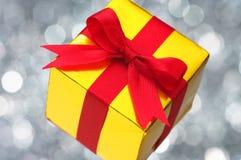 Na światła srebnym rozmytym tle złocisty prezent. Zdjęcia Royalty Free