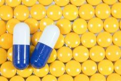 Na żółtym tle medyczne kapsuły Zdjęcia Stock