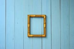 Na błękitnej deski ścianie w centrów zrozumieniach pusta złota rama fotografia stock