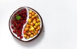Na bacia redonda do fundo branco de yin yang com as bagas do verão do corinto vermelho e da folha amarela do verde da cereja foto de stock