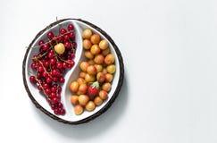 Na bacia redonda do fundo branco de yin yang com as bagas do verão do corinto vermelho e da folha amarela do verde da cereja da m fotos de stock
