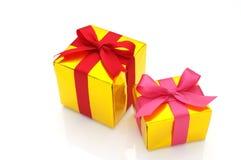 Na biały tle złociści prezenty. Zdjęcia Stock