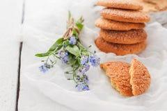 Na białym stole, piaskowatych round ciastkach, jeden łamanym i bukiecie, zdjęcie royalty free