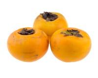 Na biały tle trzy persimmons Zdjęcia Royalty Free
