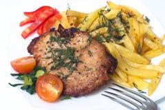 Na biel talerzu wieprzowina piec na grillu stek. Fotografia Royalty Free