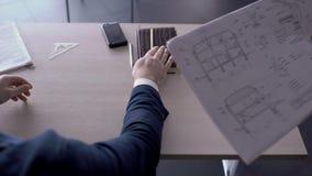 Na biurku mężczyzna zatwierdza projekt budowlanego i podpisuje kontrakt zbiory