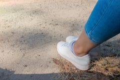 Na bocznym widoku przy kobietą foots na drodze z trawą Dziewczyna siedzi na drodze miejsce tekst fotografia stock
