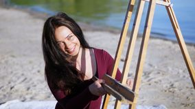 Na brzeg rzeki na plaży, przy świtem, piękny kobieta artysta przygotowywa sztalugę dla pracy uśmiechy zbiory wideo