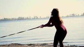 Na brzeg rzeki na plaży, przy wschodem słońca, piękna kobieta w ciasnym kostiumu chodzi z psem plewa traken, utrzymania zdjęcie wideo