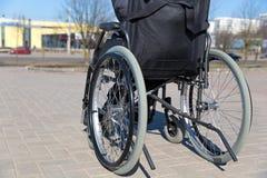 Na cadeira de rodas durante a caminhada no dia ensolarado Fotografia de Stock
