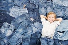 Na cajgu tle szczęśliwy dziecko. Drelichowa moda zdjęcie royalty free