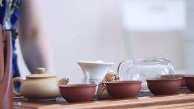 Na chaleira com água a ferver e folhas de chá põe sobre a tampa e limpe com uma escova do chá video estoque