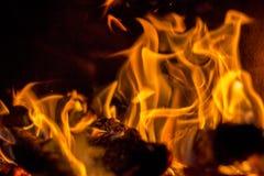 Na chaminé um fogo vermelho quente queima-se brilhantemente em um backgro escuro Foto de Stock