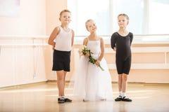 Na classe de dança do bailado: meninos novos e uma menina com flores Fotografia de Stock