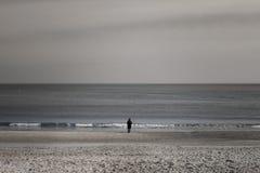 Na costa de um mar tormentoso severo está um homem imagens de stock royalty free