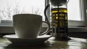 Na cozinha na tabela é um bule com chá no plano próximo é um copo foto de stock royalty free