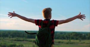 Na criança do por do sol em uma camisa vermelha uma trouxa em sua parte traseira, alcançando à parte superior em um monte alto e  vídeos de arquivo