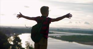 Na criança do por do sol em uma camisa vermelha uma trouxa em sua parte traseira, alcançando à parte superior em um monte alto e  video estoque