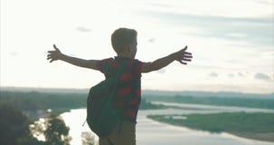 Na criança do por do sol em uma camisa vermelha uma trouxa em sua parte traseira, alcançando à parte superior em um monte alto e  filme