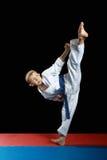 Na czarnej tła i czerwieni macie chłopiec rytmu ciosu nogi mawashi geriMawashi-geri atleta w spełnianiu w białym karategi na bla Zdjęcia Royalty Free