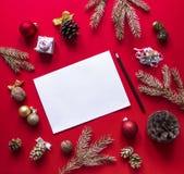 Na czerwonej malinki tła Bożenarodzeniowych dekoracjach i świerkowych złocistych gałąź układa w okręgu, bielu szkotowy ołówek Fotografia Stock