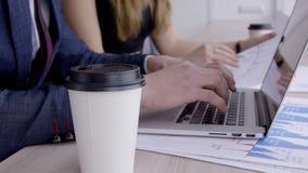 Na desktop jest kawowy, laptop, podążać ludźmi biznesu na inwestyci zbiory