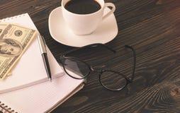 Na desktop, notatnikach, piórze, kawie i pieniądze biurowych, Zdjęcie Royalty Free