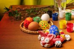 Na desktop projektant jest Wielkanocny królik Wierzb gałąź, muśnięcia, guasz i szkło woda, zdjęcia stock