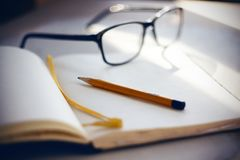 Na desktop są szkła, notatnik i ołówek, zdjęcie royalty free