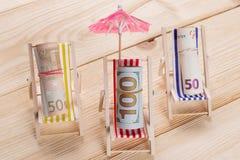 Na drewnianej podłodze tam są trzy bryczki holu w bryczka holach tam, są rolki wiele euro rachunki i dolar, tak jakby obraz stock