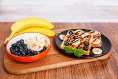 Na drewnianej tnącej desce banan i talerz z Belgijskim wafe - zdjęcie royalty free