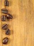 Na drewnianym biurku kawowe fasole Zdjęcia Royalty Free