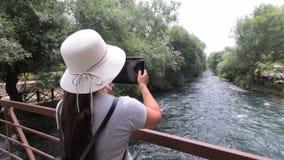 Na drewnianym moście przez rzeki dziewczyny turystę w kapeluszu na jego kierowniczym mieniu pastylka i bierze obrazki piękny zbiory