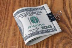 Na drewnianym stole, Amerykańscy dolarowi rachunki staczają się up i zaciskają z papierową klamerką obrazy royalty free