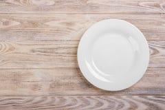 Na drewnianym stole biel pusty talerz projekta pożarniczy notatnika szablonu pisać twój zdjęcia royalty free